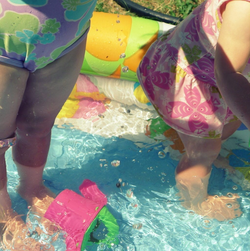 toddlers splashing in baby pool