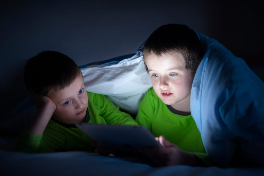 boys playing on a tablet computer electronic device in bed