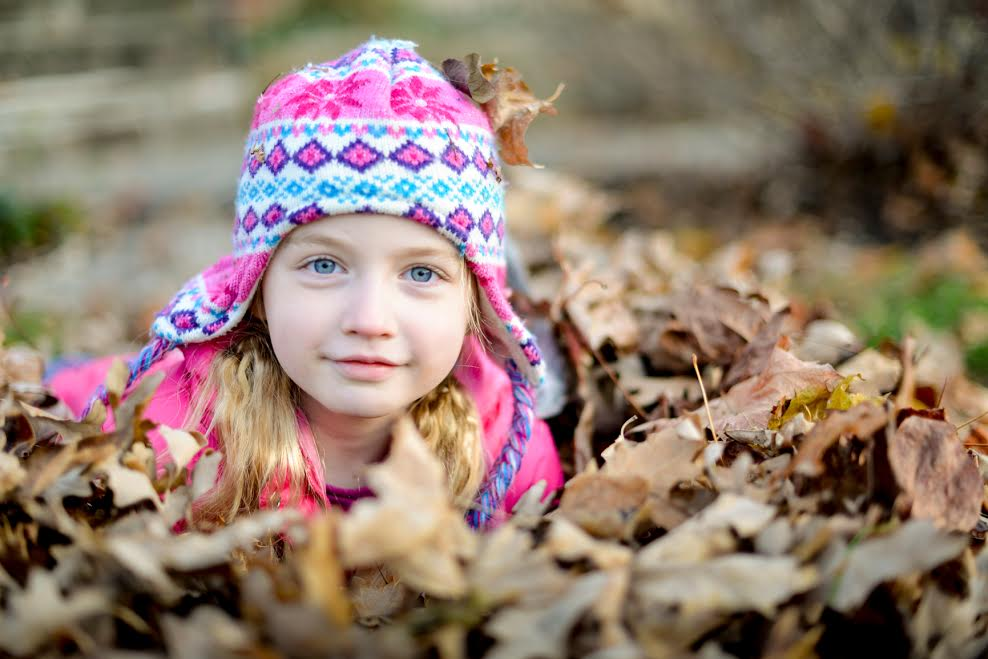 Little Girl Playing In Fall Leaves in Autumn